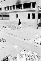 "Iraq. Baghdad. Iraqi Intelligence Service building ""Al Mokhbrat"". A woman, dressed with a black veil covering her entire body, walks near the main entrance of the building which was heavily hit by air strikes attacks (missiles) from the coalition forces (american and english army), then looted and burned by thieves, called Ali Baba. A frame with a picture of Saddam Hussein as head of state has been thrown on the ground. © 2003 Didier Ruef"