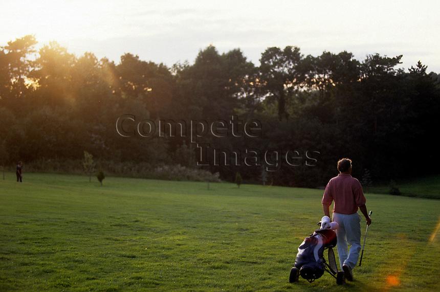 Golfer wheeling his golf bag across a golf course