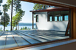 A window looking out to the Salish Sea across the metal roof of a contemporary island home.
