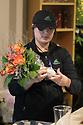 Florist in the floral department preparing a flower bouquet for sale