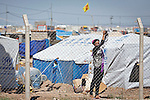 A female Syrian refugee hangs out washing on a fence in the Domiz Refugee camp near Dohuk in Iraqi-Kurdistan.  The camp, run by the UNHCR and International Rescue Committee, is home to around 4,500 refugees who have fled from the ongoing Syrian civil war with up to 400 new inhabitants arriving every day.  Built on the site of a former Iraqi Army base that was bombed during the 2003 Coalition forces invasion of Iraq, the camp was cleared of cluster bombs and unexploded ordnance by the Mines Advisory Group (MAG), a demining NGO working in Iraqi-Kurdistan.