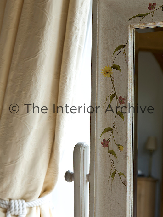 A cheval mirror with a hand-painted floral border gives the master bedroom a feminine touch