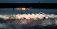 The glowing sunset above is captured and transformed by ripples in the water below.  San Francisco Bay at San Leandro Marina Park.