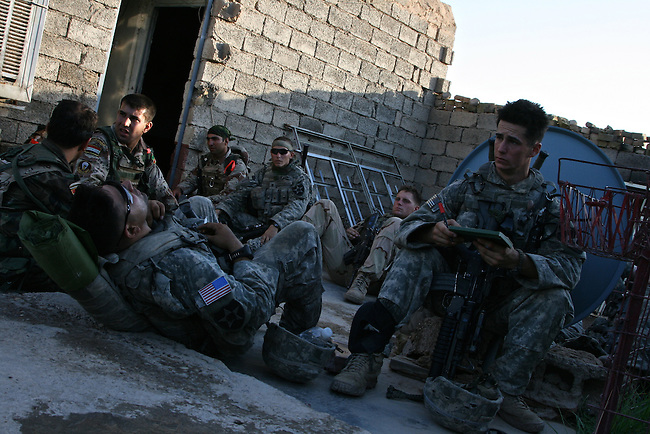 U.S. soldiers from Company C, 1st Battalion, 23rd Infantry Regiment and Iraqi troops take a break from searching houses in Baqubah, Iraq, during a U.S.-led offensive to clear insurgents from the city. June 21, 2007. DREW BROWN/STARS AND STRIPES