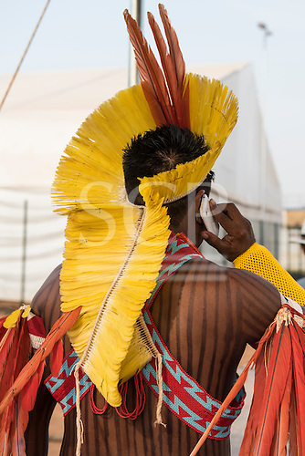 A Kayapo warrior from the remote village of Gorotire dressed in traditional feather headdress and beadwork uses an iPhone at the first ever International Indigenous Games, in the city of Palmas, Tocantins State, Brazil.