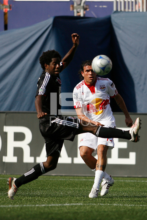Jorge Rojas (13) of the New York Red Bulls crosses the ball past Clyde Simms (19) of DC United. D. C. United defeated the New York Red Bulls 3-2 during a Major League Soccer match at Giants Stadium in East Rutherford, NJ, on April 26, 2009.