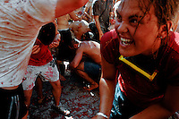 A girl fights joyfully during La Tomatina festival in Bunol, Spain, 31 August 2006. La Tomatina is a tomato fight held annually in the town of Bunol, close to Valencia. Approximately 40,000 people from all over the world arrive to fight in the battle in which about 50 tons of over-ripe tomatoes are thrown in the street. During the one hour battle everybody fights everybody by throwing squashed tomatoes. The origin of this event is unknown but the Tomatina fights have been recorded since 1945.