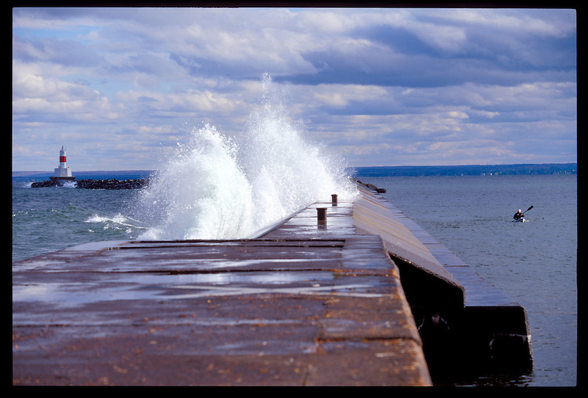 A LAKE SUPERIOR WAVE CRASHES ON THE UPPER HARBOR BREAKWATER IN MARQUETTE, MICHIGAN AS A SEA KAYAKER PADDLES IN CALM WATER ON THE OTHER SIDE.