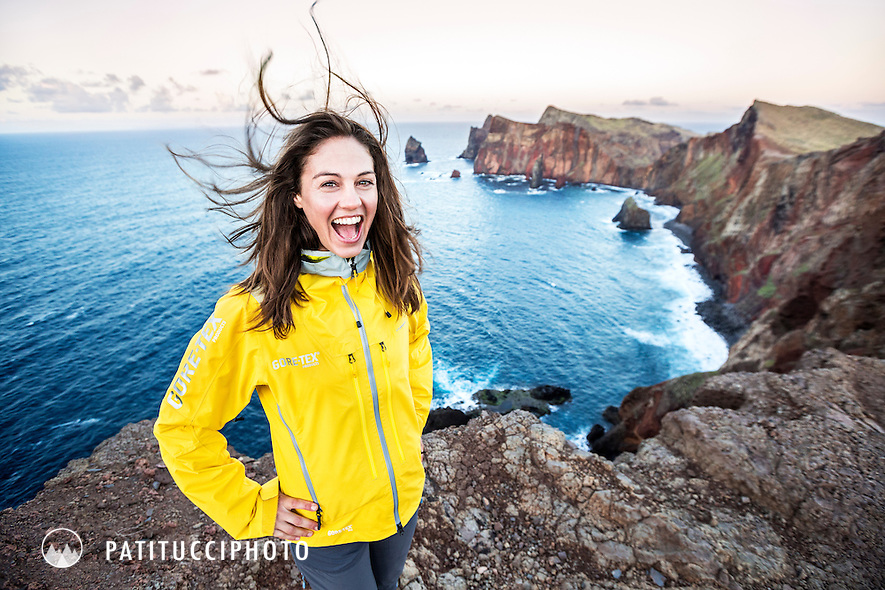 A woman hiker on the sea cliffs at Ponta Sao Lourenco smiling and enjoying the sunset as the wind blows her hair, Madeira Island