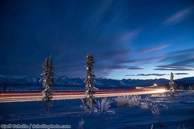 Winter landscape of vehicle car lights streaking along the Glenn Highway and the Chugach Mountains in a spruce forest taken at dusk in the Eureka area in Southcentral, Alaska   January 2016