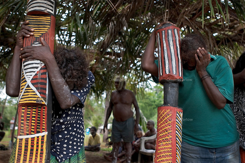 Women clutch painted poles as they grieve for loved ones who died.  This is part of the cleansing ceremony on Tiwi Islands. A cleansing ceremony is the final ceremony in the death of a family member.  A year or so after the funeral the family gets together and paints pukamani poles and places them around the grave.  Some communities won't say the name of the deceased or go back into the home until there is a big cleansing rain. <br />  Relatives of this family brought pukamani poles from Snake Bay on the other side of the island.  They continued with this ceremony even though there was an impending cyclone.