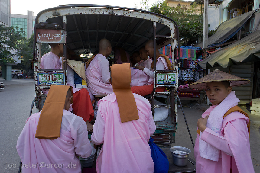nuns in the streets of Mandalay, Myanmar, 2011. Nuns are called thilashin (posessor of morality). They shave their hair, wear pink robes and take a ordination similar as monks