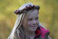 Kinder basteln mit Kastanien, Mädchen mit Kastanienkette auf dem Kopf, Kastanie