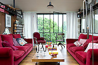 In the living room the sofa and armchairs are family pieces recovered in modern velvet and the floorboards are reclaimed railway sleepers; the coffee table is a design by Emmanuel Dougier made from a piece of oak set on antique castors