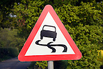 Red triangular road sign warning of slippery road