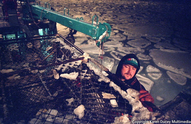 "Crewmen Larry Murphy climbs along the side of ""the stack"" on the fishing vessel ""Kiska Sea"" as it fishes for opilio crab in the arctic ice floes of the Bering Sea in January and February of 1995.  With pancake ice below death by hypothermia would be certain were he to fall overboard.  Crab pots weighing approximately 700 pounds are stacked one on top of the other.  During the 1990's the pot limit was 250 pots for larger vessels such as this one.  The Bering Sea is known for having the worst storms in the world.  Nights are long and cold in the arctic in the winter.  Crab fishing in the Bering Sea is considered to be one of the most dangerous jobs in the world.  This fishery is managed by the Alaska Department of Fish and Game and is a sustainable fishery.  The Discovery Channel produced a TV series called ""The Deadliest Catch"" which popularized this fishery."