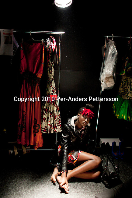 CAPE TOWN, SOUTH AFRICA - AUGUST 13: A model waits backstage to be dressed before a show with Stoned Cherrie, a fashion label, at the African Fashion International Cape Town fashion week on August 13, 2010, at the Cape Town International Convention Center, in Cape Town, South Africa. Stoned Cherrie is founded by Nkhensani Nkosi, age 37, a mother of four and a celebrated fashion designer, entrepreneur, television personality and an actress in South Africa. She launched her new collection Love Movement at this event. (Photo by Per-Anders Pettersson)