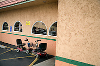 A pair of motorized scooter chairs sit parked outside of a Mexican restaurant in Pendleton, Oregon, USA.