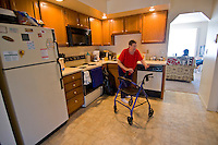 A 80-85 year old woman reachs for her walker in her kitchen.