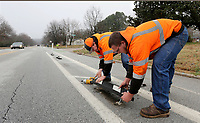 Clayton Jones (left) and Blayne Marryman, both with the city of Fayetteville's Transportation Division, reset a curb stop   that had been damaged by traffic Monday, February 10, 2020, as part repairs and adjustments to a bike lane on Rolling Hills Drive in Fayetteville. The lane was constructed by Bike NWA through grant funding from the Walton Family Foundation. Check out nwaonline.com/200211Daily/ and nwadg.com/photos for a photo gallery.<br /> (NWA Democrat-Gazette/David Gottschalk)