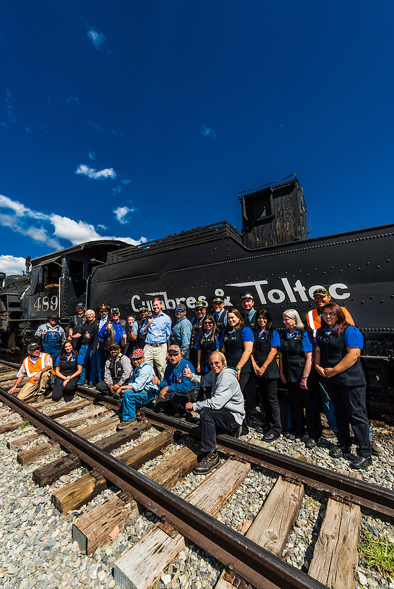 Governor John Hickenlooper (of Colorado) poses with two train crews at the meeting point at Osier, Colorado  on a visit to the the Cumbres & Toltec Scenic Railroad, from Antonito to Osier, Colorado during peak autumn color. The Cumbres & Toltec Scenic Railroad has been jointly owned by the States of Colorado and New Mexico since 1970 when it was purchased from the Denver and Rio Grande Western Railway, which was going to scrap the line. The train makes a 64 mile run between Antonito, Colorado and Chama, New Mexico. The railroad is the highest and longest narrow gauge steam railroad in the United States with a track length of 64 miles. The train traverses the border between Colorado and New Mexico, crossing back and forth between the two states 11 times. The narrow gauge track is 3 feet wide. It runs over 10,015 ft (3,053 m) Cumbres Pass.