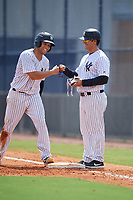 GCL Yankees East Raymundo Moreno (left) fist bumps coach Hector Rabago (right) during a Gulf Coast League game against the GCL Phillies East on July 31, 2019 at Yankees Minor League Complex in Tampa, Florida.  GCL Yankees East defeated the GCL Phillies East 11-0 in the first game of a doubleheader.  (Mike Janes/Four Seam Images)