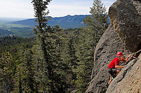Photo story of Philmont Scout Ranch in Cimarron, New Mexico, taken during a Boy Scout Troop backpack trip in the summer of 2013. Photo is part of a comprehensive picture package which shows in-depth photography of a BSA Ventures crew on a trek. In this photo, a BSA Venture Crew  member  climbs the front face of a natural rock, 50- feet off of the ground. The climbing was taking place at the  Cimarroncito Camp in the backcountry at Philmont Scout Ranch.   <br /> <br /> The  Photo by travel photograph: PatrickschneiderPhoto.com