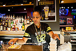 Bartender Tara Marshall cleans the bar at closing at Buffalo Wild Wings in Concourse D at Hartsfield–Jackson Atlanta International Airport, in Atlanta, Georgia on August 28, 2013.