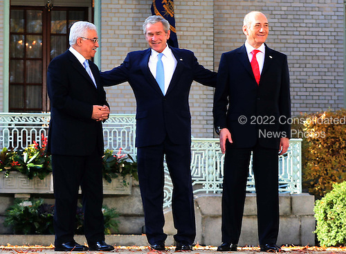 President George W. Bush reaches out to  Israeli Prime Minister Ehud Olmert on right and Palestinian Authority President Mahmoud Abbas on left, at the .Middle East Peace Conference  at the U. S Naval Academy in Annapolis, Maryland on November 27, 2007.Agency pool photo by Dennis Brack/Black Star