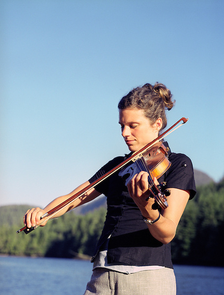BRITISH COLUMBIA,CANADA : Sarah Hart plays fiddle for guests during cocktail hour at Nimmo Bay Resort. . Nimmo Bay is an angler's paradise set in the wilderness of mainland British Columbia, near the Broughton Archipelago off the northeast tip of Vancouver Island. Nimmo Bay offers spectacular scenery and access to some of the world's best salmon and trout fishing. Nimmo Bay Resort has pioneered helicopter fishing and helicopter adventures over the last 25 years. Helicopters take guests to remote coastal rivers and magical fishing holes for fabulous catch and release salmon and trout fly fishing. Nimmo Bay, British Columbia, Canada.
