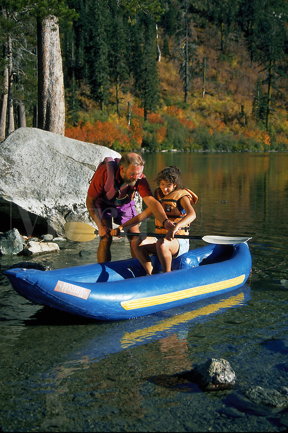 Father and daughter on inflatable kayaking trip on the lake in autumn