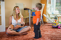 A woman sitting crossed-legged at home on her living room carpet, listening to her toddler son and  breastfeeding her baby.<br /> <br /> 09/07/2011<br /> Hampshire, England, UK