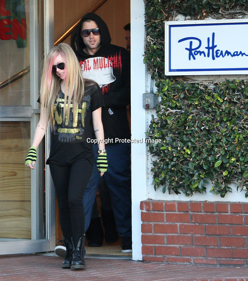 .December 7th 2010 ..Avril Lavigne walking with Brody Jenner  wearing a Metal Mulisha hooded sweater .shopping at fred Segal in West Hollywood California. The couple was hugging and kissing while inside shopping for over and hour.  Avril was laughing & smiling wearing dark blue blocker sunglasses & lime green fingerless gloves to match her untied black Dr. Doc Martens army combat boots. Pink & green hair gold skull NTH shirt ..Abilityfilms@yahoo.com.805-427-3519.www.AbilityFilms.com