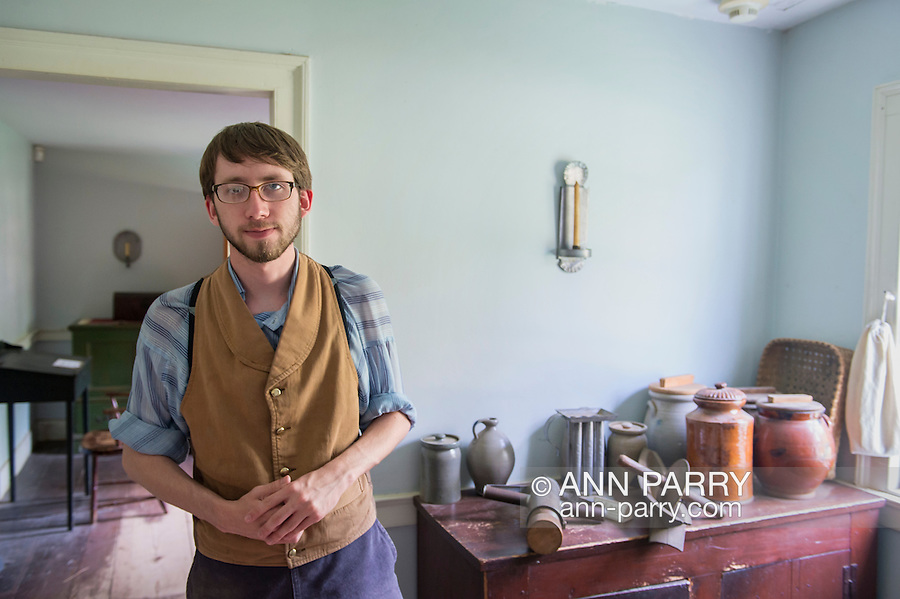 Old Bethpage,  York, USA. 30th August, 2015. Matt, a seasonal staff member wearing traditional style American clothing, gives a tour of the Powell House during the Old Time Music Weekend at Old Bethpage Village Restoration. An old-fashioned sausage maker is on the cabinet corner next to him. The house was built in 1750 and is restored to its expanded 1855 size, and is the only building standing on its original location in the village.