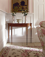 A detail of a traditional room with pink and white striped wallpaper and part panelled walls. Two floral pattern pottery vases and a bowl are arranged on an elegant Georgian side table. A rug on the tiled floor and the upholstery reflect the pink floral theme.