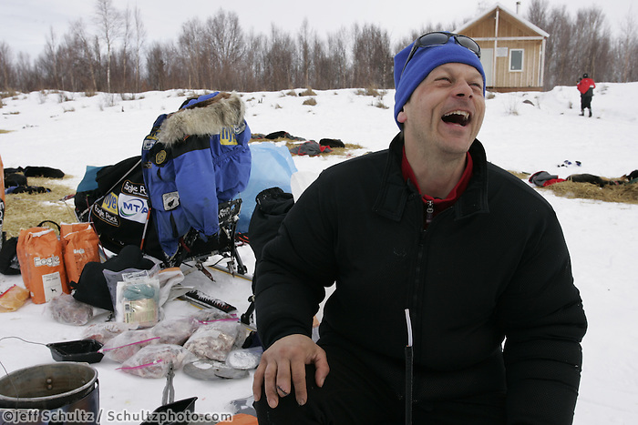 Martin Buser laughs while chatting with friends at the half-way Iditarod checkpoint. You can see his cut-off finger on his right hand. 2005 Iditarod Trail Sled Dog Race.