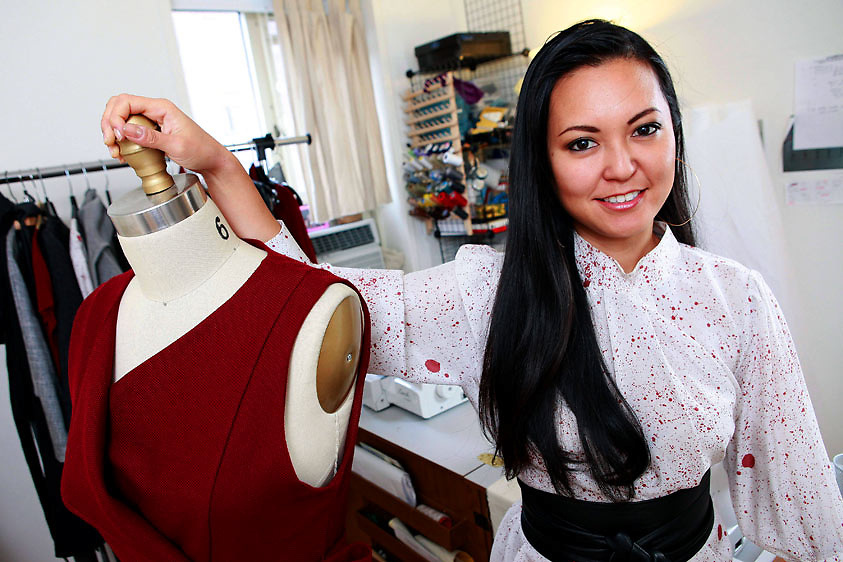 Fashion designer Ivy Higa, 30, in her work space/apartment in Manhattan, NY.  Higa, a contestant on season 8 of Project Runway, is wearing one of her own creations while standing next to a mannequin bust with a piece from her Spring 2010 collection...
