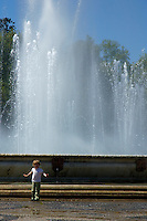 Little girl playing next to a water fountain on the Plaza de Espana in Seville, Andalusia, Spain.