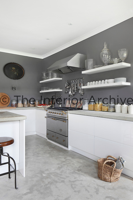 Storage jars are neatly arranged on the work surfaces, whilst crockery and glassware is stored on open shelving above