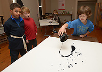 NWA Democrat-Gazette/ANDY SHUPE<br /> Isaiah Cosmos-Key, 8, (from right) slings paint onto a canvas Wednesday, Jan. 3, 2018, as fellow students Elliot Chyrchel, 7, and Traelen Roscoe, 7, watch during BLACKOUT, a youth art camp at Artist's Laboratory Theatre in Fayetteville. The eight-day pay-what-you-can camp is exploring the affect of light and dark through art, performance and science experiments and runs through Friday.
