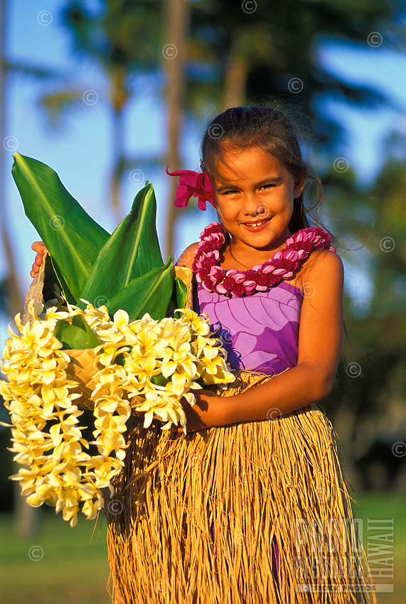 Young hula girl, in grass skirt, age 8, holding plumeria flower leis in basket