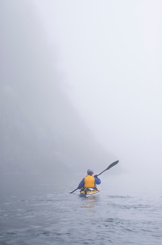 A sea kayaker paddles through the fog in Lake Superior Provincial Park near Wawa Ontario Canada.