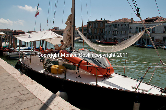 A boy relaxes in a makeshift hammock, reading a book, on his boat, while docked at Murano Island outside of Venice, Italy