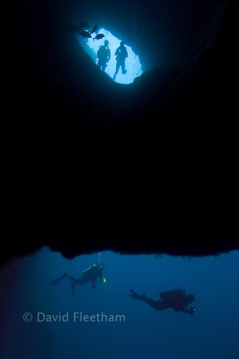 Divers (MR) entering Blue Hole, on of Palau's favorite dive sites. Micronesia.