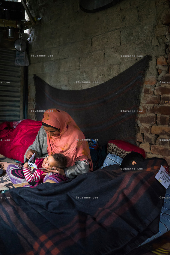 Shugufta, 29, plays with Zainab, 10 months, as her other children take a nap in their temporary shelter in Narbal village, Jammu and Kashmir, India, on 24th March 2015. When the floods hit in the middle of the night, Shugufta and her family had to walk 5 miles to find shelter. Save the Children supported the family with shelter kits, blankets, hygiene items, food and tarpaulin, which they have used to build a temporary shelter next to their crumbled home. Photo by Suzanne Lee for Save the Children