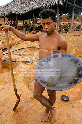 Ouro Verde garimpo, Para State, Brazil. Man holding a gold pan with gold deposit in the centre.
