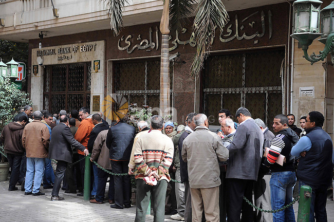 Customers queue at Egypt banks in Cairo February 6, 2011. Egypt banks to allow transfers, limit cash withdrawals . Egypt's banks open today for the first time in more than a week amid investor concern that a possible run on deposits may weaken the currency and raise government borrowing costs.  Photo by Karam Nasser