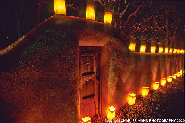The adobe walls and wooden gates of Canyon Road in Santa Fe, New Mexico, are aglow with faralitos, small candles in  paper bags, on Christmas Eve