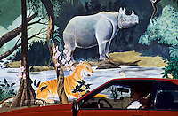 Man in his reed car in front of a beautiful wall painting of a rhino and tiger