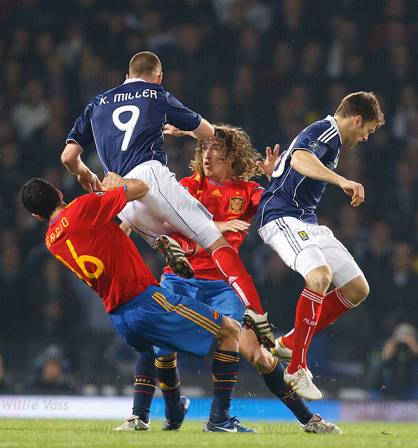 Kenny Miller and Jamie Mackie go over the top as they battle with Carles Puyol and Sergio